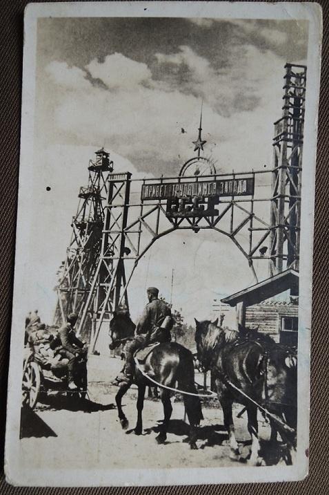 """Немецкие солдаты на фоне надписи на воротах """"Привет трудящимся запада"""""""